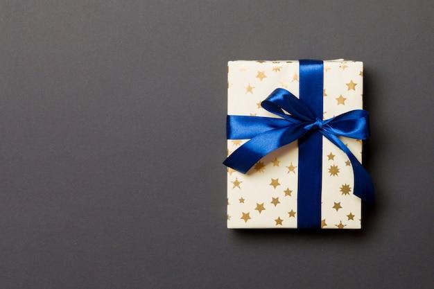 Cadeau de noël fait à la main emballé dans du papier avec un ruban bleu sur fond noir