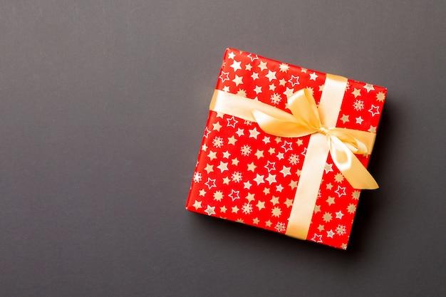 Cadeau de noël fait à la main emballé dans du papier avec un ruban doré sur fond noir