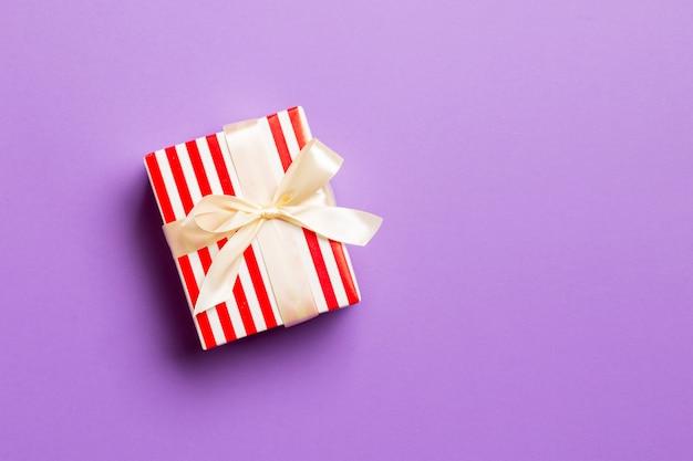 Cadeau de noël fait à la main emballé dans du papier avec un ruban jaune sur violet