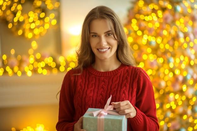 Cadeau de noël femme debout avec un cadeau dans ses mains