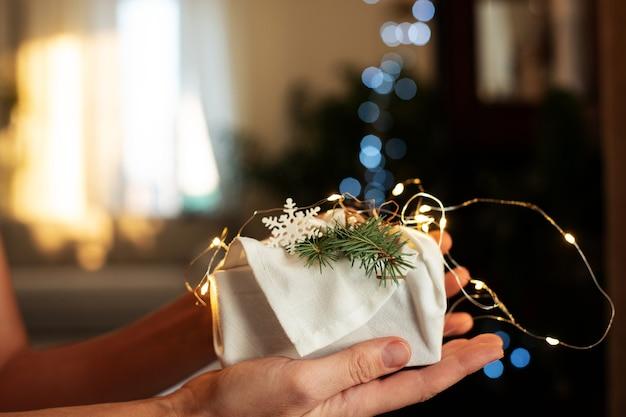 Cadeau de noël en mains. emballage dans des matériaux écologiques avec éclairage