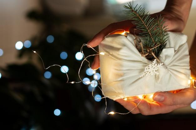 Cadeau de noël en mains. emballage dans des matériaux écologiques