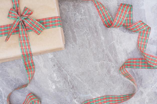 Cadeau de noël avec noeud festif sur fond de marbre.