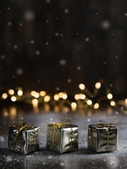 Cadeau de noël avec des ornements d'or sur fond sombre