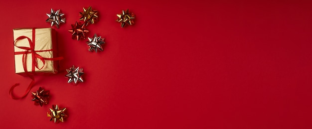 Cadeau de noël en papier doré avec un ruban rouge