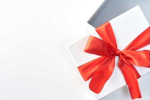 Un cadeau de noël en papier d'emballage blanc et rubans rouges