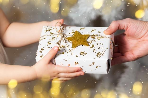 Cadeau de noël, père et fille, mains tenant un cadeau blanc, mise au point sélective.