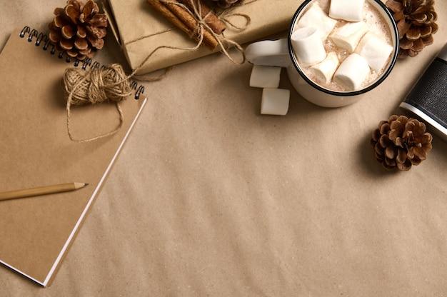 Cadeau de noël recadré dans du papier cadeau d'emballage artisanal, cannelle attachée avec une corde, des pommes de pin, un appareil photo vintage, un bloc-notes et une tasse avec du cacao et des guimauves sur fond de tableau noir avec espace de copie pour l'annonce