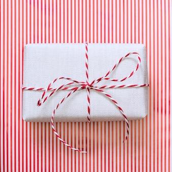 Cadeau de noël avec ruban rouge sur la surface des rayures.