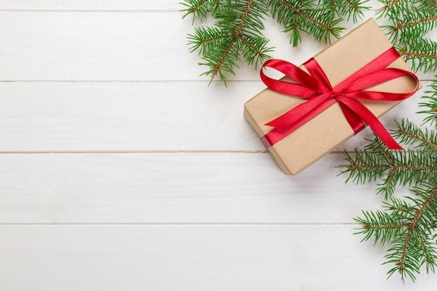 Cadeau de noël surface noël avec des branches de sapin sur une surface blanche en bois avec espace de copie