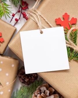 Cadeau de noël avec vue de dessus d'étiquette cadeau carrée vierge, maquette