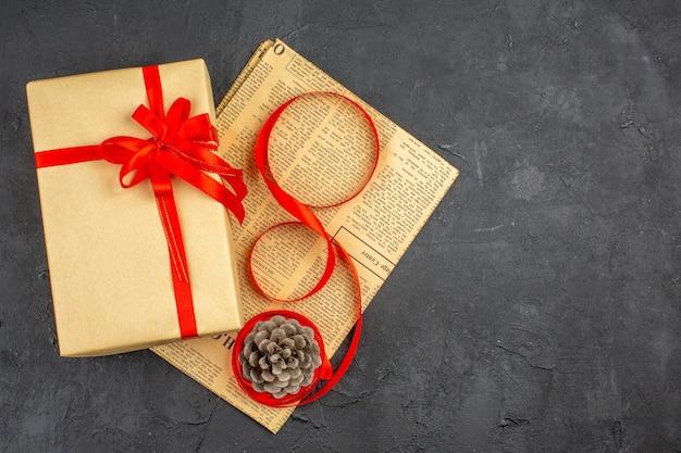 Cadeau de noël vue de dessus en ruban de papier brun sur papier journal sur une surface sombre