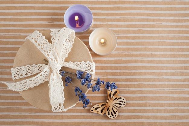 Cadeau avec noeud en dentelle, fleur de lavande, bougie allumée