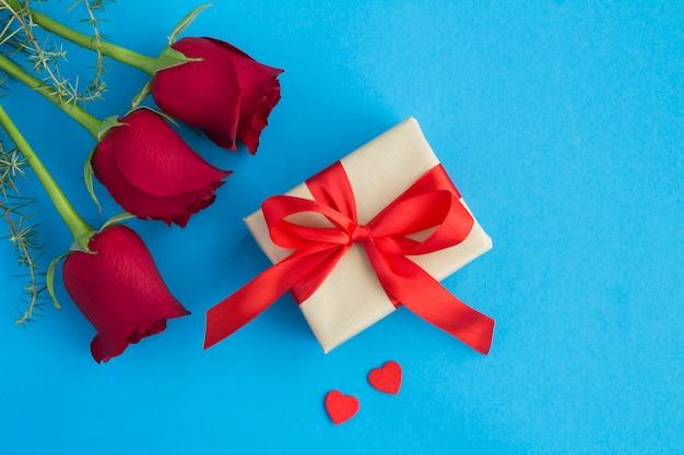 Cadeau avec noeud rouge, roses rouges et coeurs rouges sur bleu