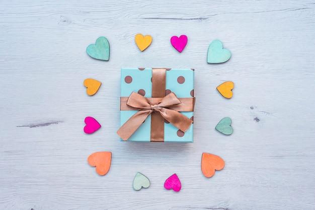 Cadeau avec noeud sur table en bois, avec des coeurs