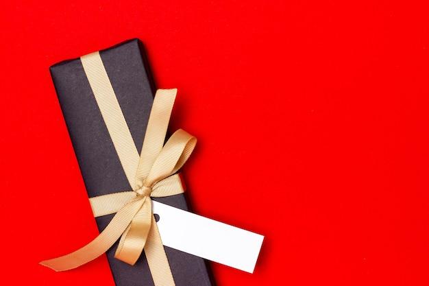 Cadeau noir avec étiquette blanche vierge sur fond rouge.