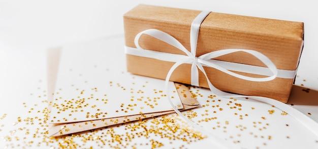 Cadeau et note vierge avec enveloppe, étoiles de paillettes d'or sur blanc