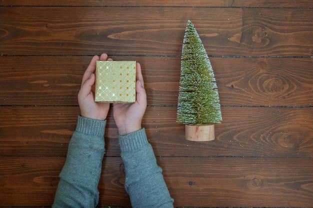 Cadeau d'or dans les mains des enfants et petit arbre de noël sur fond de bois