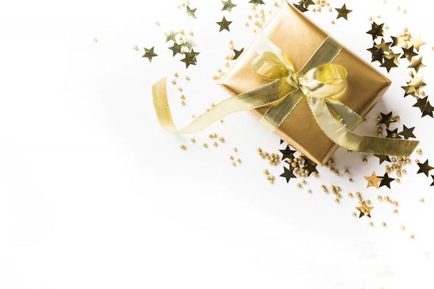 Cadeau d'or avec un décor de luxe brillant sur blanc. mise à plat. vue d'en-haut. noël.