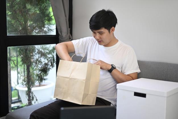 Cadeau d'ouverture de jeune homme asiatique dans le salon.