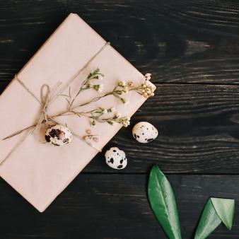 Cadeau en papier kraft, oeufs de caille, branches de saule, oreilles de lapin et décorations sur fond sombre