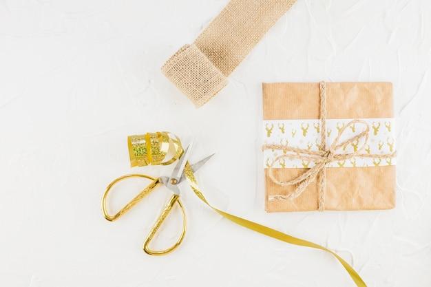 Cadeau en papier kraft près de ciseaux et ruban