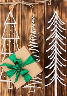Cadeau en papier kraft avec un ruban vert sur un fond de bois brûlé rustique avec des arbres de noël peints. vue de dessus. espace de copie. concept de nouvel an et de noël