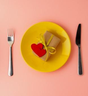 Cadeau, paquet de papier brun kraft, deux cœurs en feutre sur une plaque jaune, saint-valentin.
