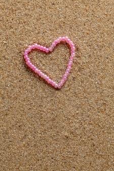 Cadeau perles en forme de coeur sur fond de sable.