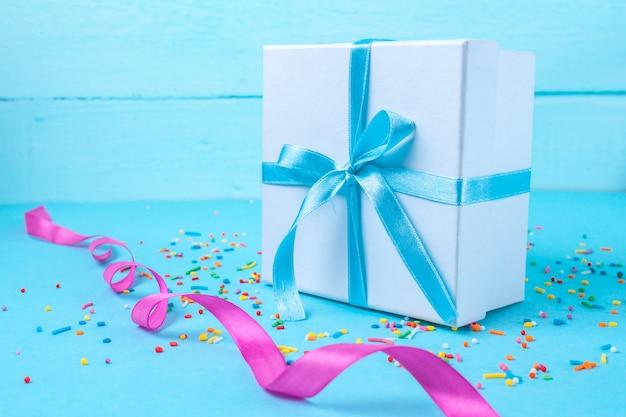 Cadeau, petite boîte attachée avec un ruban de satin bleu. concept de cadeau. surprises et cadeaux pour vos proches, félicitations pour les vacances, offrez des cadeaux
