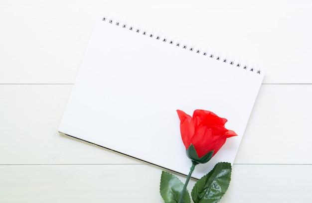Cadeau présent avec fleur rose rouge et cahier sur une table en bois