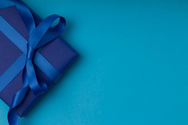 Cadeau romantique emballé et décoré avec un arc sur fond bleu avec espace copie