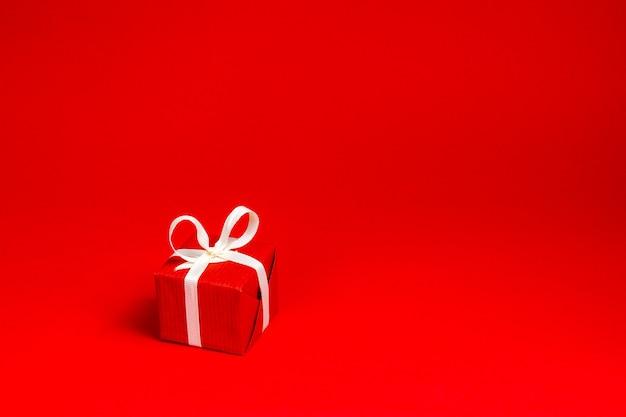 Cadeau rouge avec ruban blanc sur fond rouge.