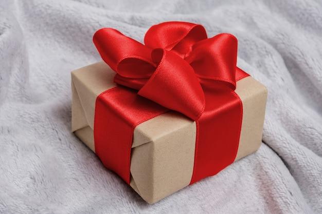 Cadeau avec un ruban rouge sur un couvre-lit gris ou une couverture