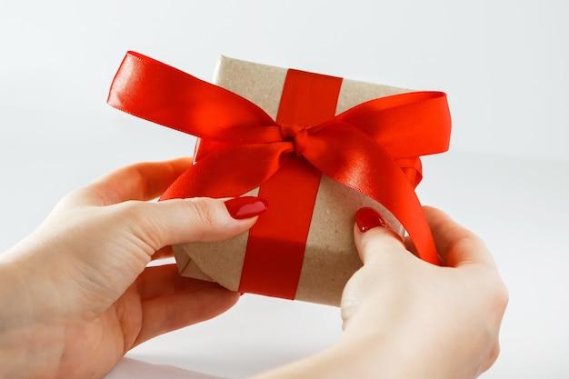Cadeau avec un ruban rouge dans les mains sur une surface blanche. cadeau de la saint-valentin dans les mains de la femme - coffret en papier kraft et ruban de satin rouge.