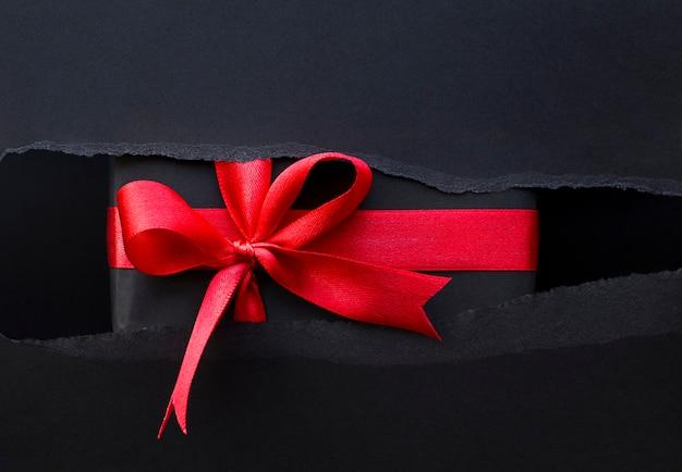 Cadeau avec un ruban rouge dans un papier déchiré noir. vendredi noir
