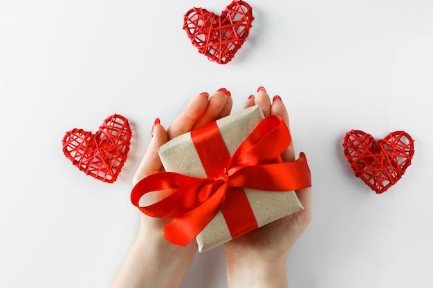 Cadeau avec un ruban rouge en mains sur fond blanc.