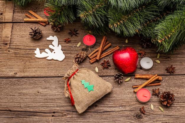 Cadeau en sac, arbre du nouvel an, pomme, bougies, épices, cerfs, cônes. décorations nature, planches en bois vintage