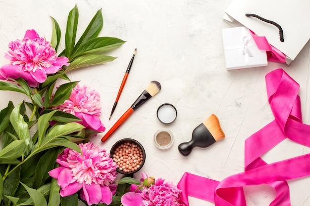 Cadeau sac blanc et emballé avec cadeau, pinceau blush, fard à paupières et ruban rose et pivoines. vue de dessus.