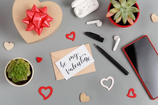 Cadeau de la saint-valentin et be my valentine card près de coeurs, plantes succulentes, écouteurs et smartphone sur tableau gris
