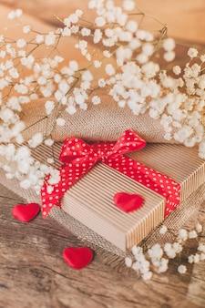 Cadeau de la saint-valentin sur bois avec des décorations rouges
