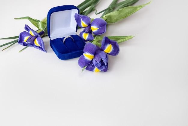 Cadeau saint valentin - bouquet de fleurs d'iris bleu et bague de fiançailles dans une boîte en velours bleu