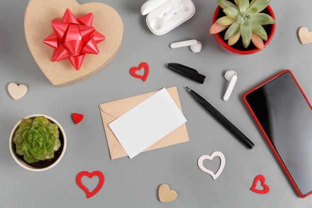 Cadeau de la saint-valentin et carte noire près de coeurs, plantes succulentes, écouteurs et smartphone