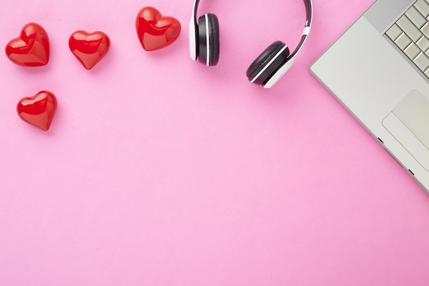 Cadeau de la saint-valentin en copyspace décoration de vacances coffret rouge avec un arc rouge sur fond rose avec des coeurs rouges bannière web de vacances