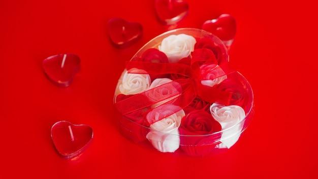 Cadeau de saint valentin sur fond rouge. beaucoup de roses rouges et blanches dans un emballage en forme de cœur, attaché avec un ruban rouge. la notion d'amour