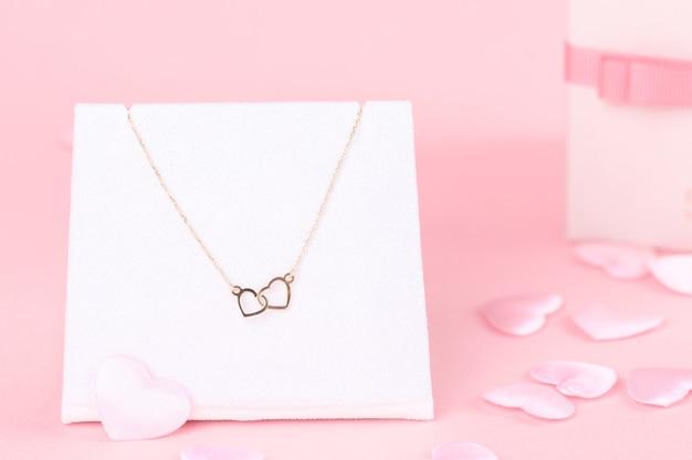 Cadeau de saint valentin pour elle, bracelet avec deux coeurs sur fond rose, espace copie