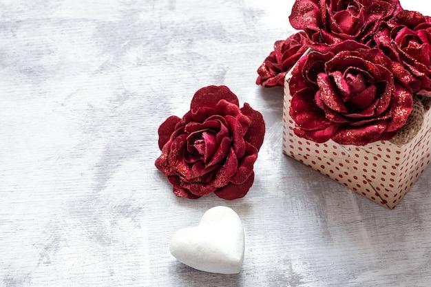 Cadeau de la saint-valentin avec des roses décoratives et un coeur blanc sur l'espace de copie de fond clair.