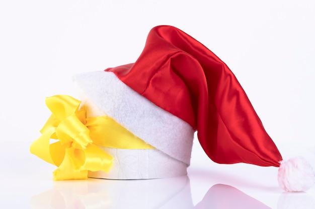 Cadeau sous forme de rouleau de papier toilette avec un noeud jaune, sous le chapeau du père noël. espace de copie.