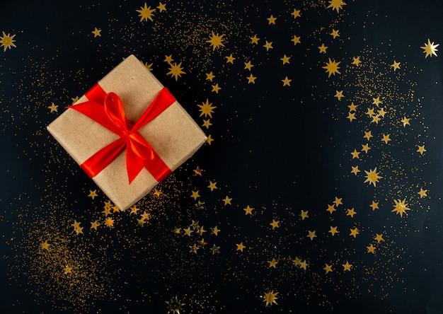 Cadeau de vacances attaché avec un ruban rouge sur fond noir de noël