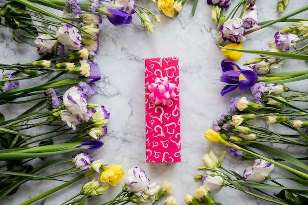 Cadeau de vacances. coffret cadeau avec décorations florales sur fond de marbre.eustoma, iris, oeillets
